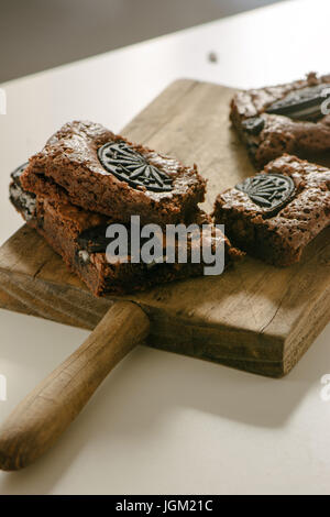 Chocolate brownies, with black biscuit stuffed with cream on table - Stock Photo