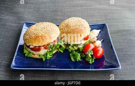 Healthy fast food burgers, homemade rye buns with sesame, burger with beluga lentils and hemp seeds, on canvas background - Stock Photo