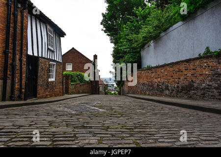 Top of the steep hill in Lincoln, looking back down into the town down a old brick road with old buildings - Stock Photo