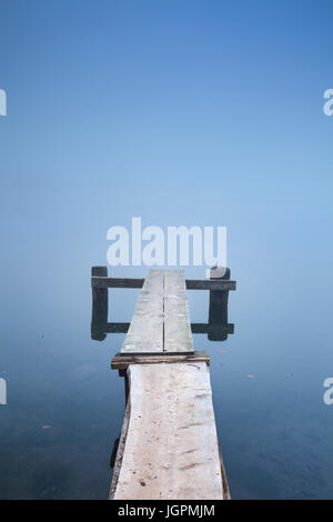 A small jetty on Bohinj Lake in Slovenia on a misty morning. - Stock Photo