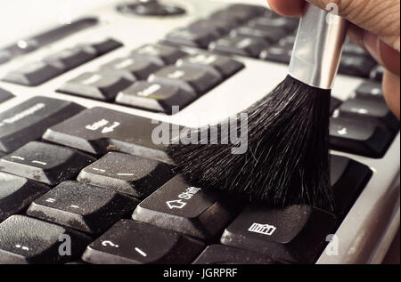 cleaning keyboard with brush. removing dust from a dirty keyboard on the compute - Stock Photo