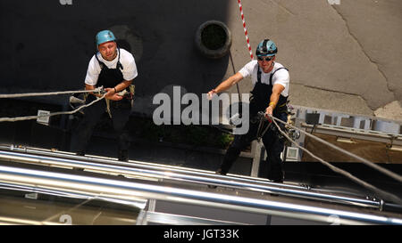 Workers hanging on climbing ropes, showing thumb up sign. - Stock Photo