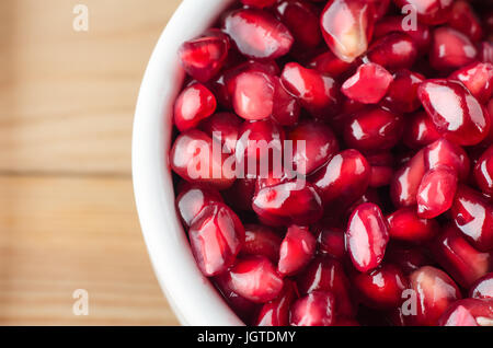 Overhead macro shot of a white bowl filled with red pomegranate seeds on a wooden table. - Stock Photo