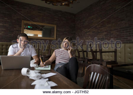 Diner owners working at laptop and talking on cell phone - Stock Photo
