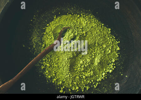 Japanese Matcha green tea powder in dark wooden bowl with spoon, top view. Clean eating, healthy, diet food concept - Stock Photo