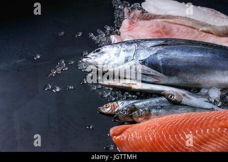 Variety of raw fresh fish. Whole tuna and herring, fillet of salmon, cod, red fish on crushed ice over dark wet - Stock Photo