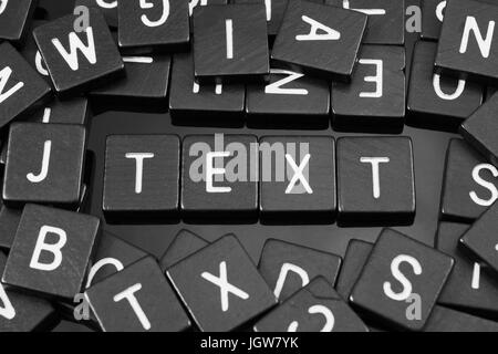 Black letter tiles spelling the word 'text' on a reflective background - Stock Photo