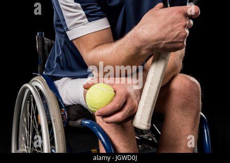 Cropped shot of disabled sportsman sitting in wheelchair and holding tennis racquet with ball - Stock Photo
