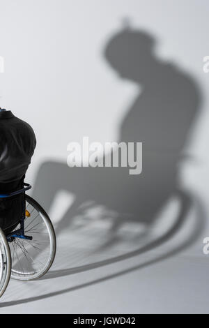 cropped shot of physically handicapped man in wheelchair with his shadow on wall - Stock Photo