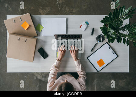 top view of businesswoman working with laptop computer on workplace in office - Stock Photo