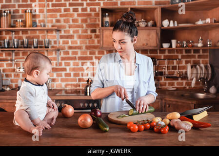 Happy young family cooking breakfast together. Mother chopping cucumber on cutting board while her son sitting near - Stock Photo
