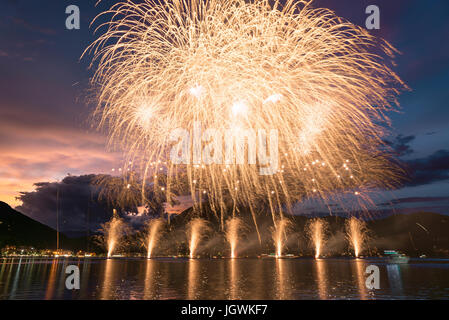Fireworks on the Lugano Lake in a summer evening with cloudy sky at the sunset in the background - Stock Photo