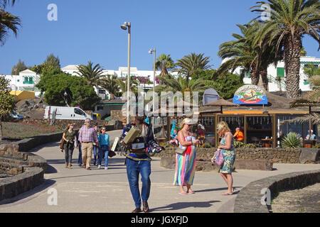 Afrikanischer Strassenhaendler verkauft Armbanduhren an der Promenade beim Badestrand Playa de las Cucharas, Costa - Stock Photo