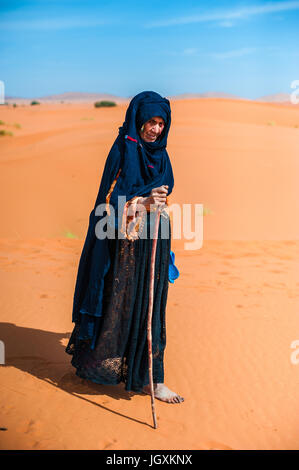 old  berber woman walking alone on a sand dune in Merzouga, Morocco - Stock Photo
