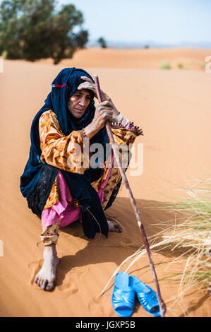 Portrait of old Berber woman sitting on a sand dune in Merzouga, Morocco - Stock Photo