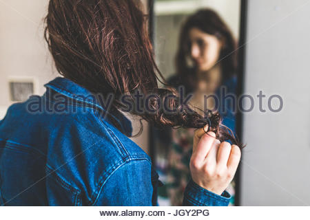 Young woman standing in front of mirror, pulling hair-band from hair, rear view - Stock Photo