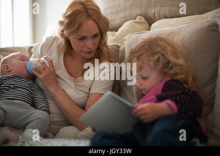 Mother feeding baby son and helping daughter with digital tablet - Stock Photo