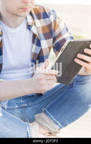 A man in smart casual hipster style with tablet combining work with relax on the beach of Baltic Sea - Stock Photo
