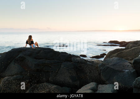 A healthy young girl sits on a boulder and watches the sunset over a magnificent seascape in Australia. - Stock Photo