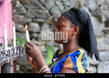 African woman lighting candles in church. Lome. Togo. - Stock Photo