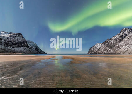 Sandy beach and snowy peaks framed by the Northern Lights in the polar night, Ersfjord, Senja, Troms, Norway - Stock Photo