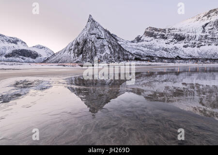 Snowy peaks reflected in the frozen sea surrounded by sandy beach at dawn, Ersfjord, Senja, Troms, Norway, Scandinavia, - Stock Photo