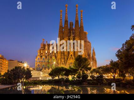 La Sagrada Familia church lit up at night designed by Antoni Gaudi, UNESCO, reflected in pool, Barcelona, Catalonia, - Stock Photo