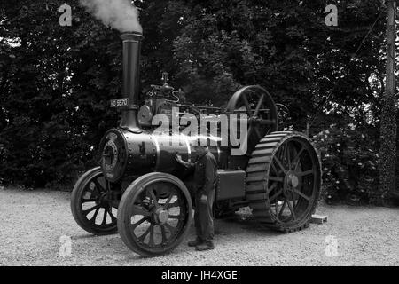 Black and White shot of a steam traction engine. Driver polishing the boiler on a machine that is in full steam - Stock Photo