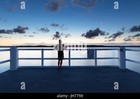 A person watches the sea alone from a pier after dusk in Australia. - Stock Photo