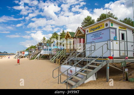 An HM Coastguard station and rows of beach huts on a sandy beach in Norfolk, UK that is closed representing a beach - Stock Photo
