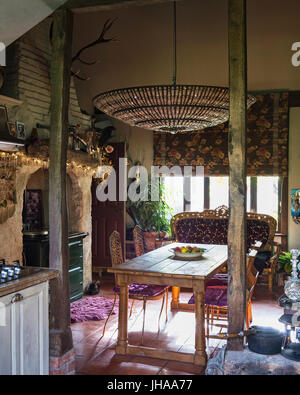 Chandelier over table in rustic dining room - Stock Photo