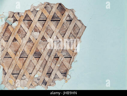 Part of the wall of the old house with partially peeled plaster where the wooden crate can be seen - Stock Photo
