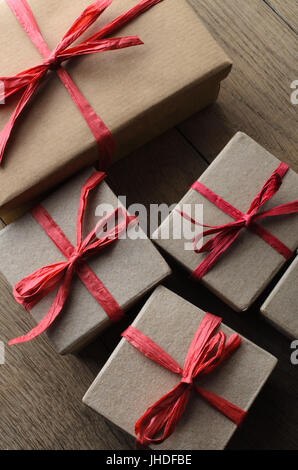Overhead shot of simple plain brown and paper wrapped gift boxes for Christmas, tied to a bow with red raffia ribbon, - Stock Photo