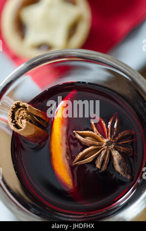 Overhead close up of a glass of spicy mulled wine with star topped Christmas mince pie on red napkin in soft focus - Stock Photo