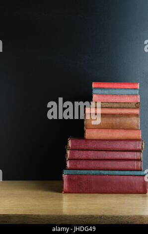 A pile of old, used text books stacked in a pile on a wooden desk in front of a black chalkboard.  Copy space to - Stock Photo