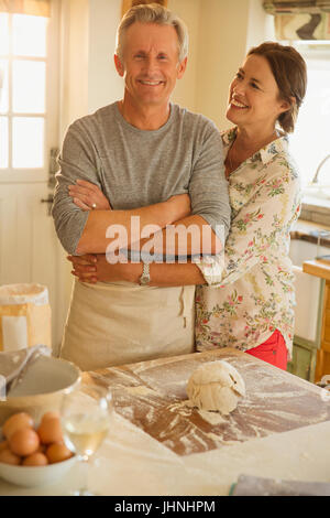 Smiling affectionate couple hugging, baking in kitchen - Stock Photo