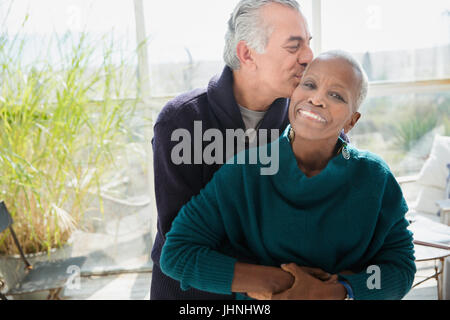 Portrait affectionate senior couple hugging and kissing - Stock Photo