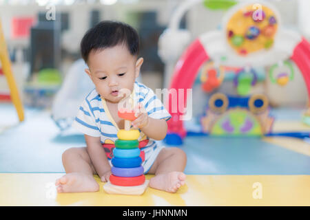 Adorable Asian baby boy 9 months sitting and playing with color developmental toys in kids room at home. - Stock Photo