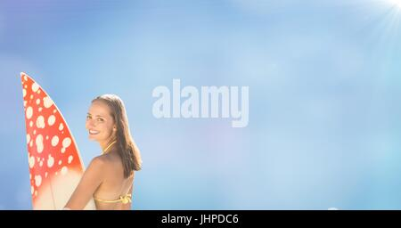 Digital composite of Back of surfer woman against blurry blue background with flare - Stock Photo