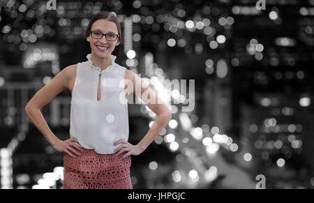 Portrait of smiling businesswoman wearing eyeglasses standing with hands on hip against defocused image of illuminated - Stock Photo