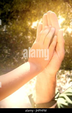 Close-up of hand giving high five  against trees in forest - Stock Photo