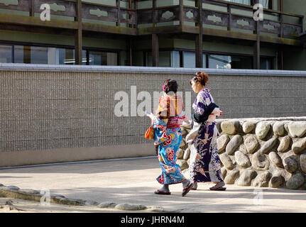 Hiroshima, Japan - Dec 28, 2015. Women in kimono walking on the road in Miyajima island, Japan. Miyajima is famous - Stock Photo