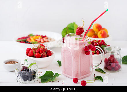 Yoghurt-strawberry smoothies in a jar on a white background - Stock Photo