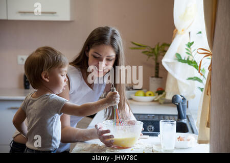 mother and young son prepare pie in the kitchen - Stock Photo
