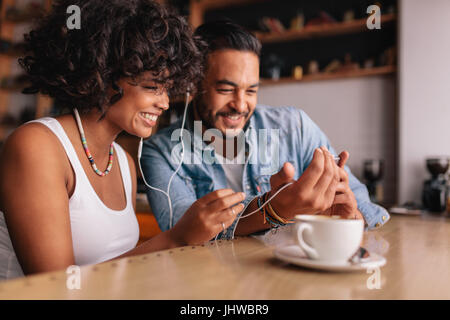 Happy young couple sitting at coffee shop having video chat on mobile phone. Young man and woman with earphones - Stock Photo