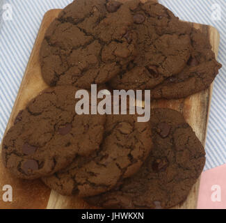 Double chocolate chip cookies on breadboard - Stock Photo