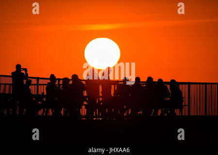 Aberystwyth, Wales, UK. 16th July, 2017. UK Weather: People sitting on the end of Aberystwyth's Victorian seaside - Stock Photo