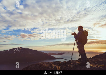 photographer with tripod taking panorama of beautiful nature landscape in Norway at sunset, silhouette of man with - Stock Photo