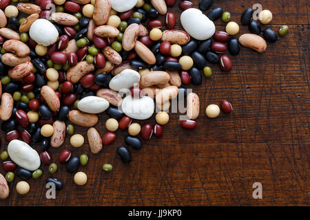 Mixed dry beans on dark wood from above. Space for text. - Stock Photo