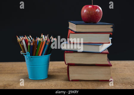 Apple on book stack with color pencils on table against black background - Stock Photo
